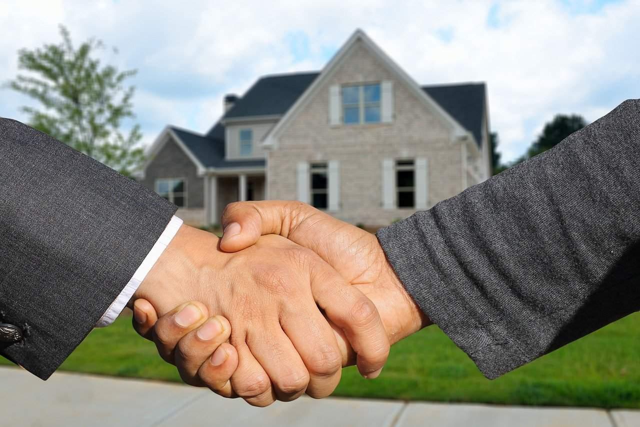 אנשים לוחצים ידיים ברקע רואים בית חדש